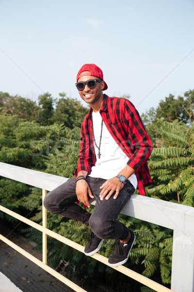 Cheerful dark skinned young guy wearing sunglasses Stock photo © deandrobot