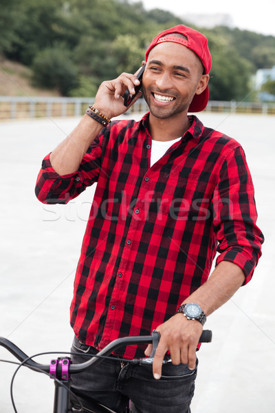 Happy dark skinned boy talking at phone on bicycle Stock photo © deandrobot