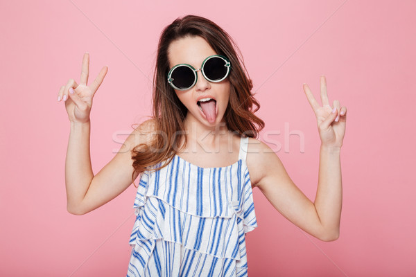 Funny amusing young woman showing tongue and having fun Stock photo © deandrobot