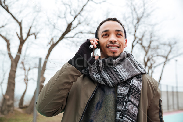Handsome young african man talking by phone. Stock photo © deandrobot