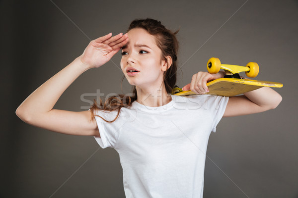 Young teenage girl holding skateboard and looking into the distance Stock photo © deandrobot
