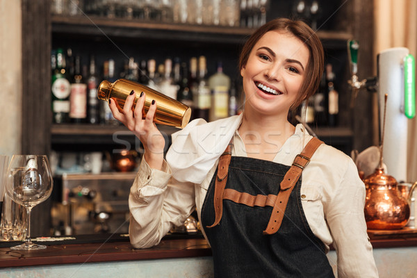Pretty young woman standing in cafe holding shaker. Stock photo © deandrobot