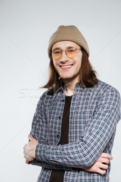 Vertical image of Smiling hipster in eyeglasses with crossed arms Stock photo © deandrobot
