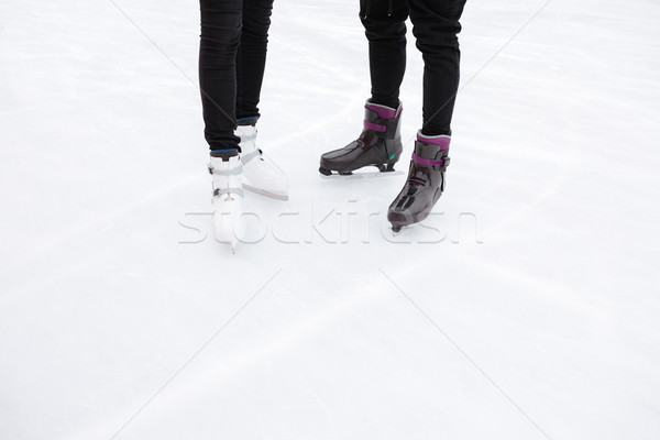 Cropped picture of young loving couple skating at ice rink Stock photo © deandrobot