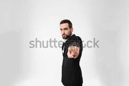 Handsome young bearded businessman pointing to camera. Stock photo © deandrobot