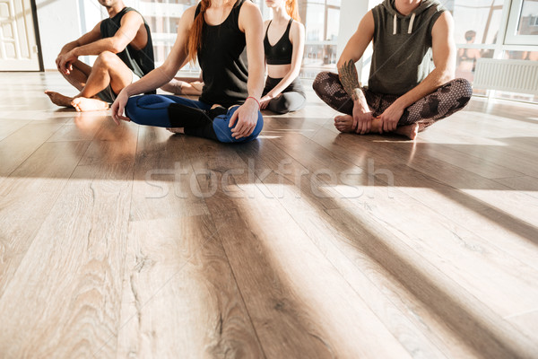 Pessoas do grupo sessão as pernas cruzadas ioga estúdio Foto stock © deandrobot