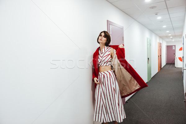 Nő piros kabát sétál folyosó elegáns Stock fotó © deandrobot