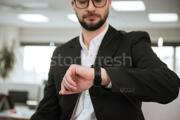 Cropped image of Bearded business man looking at wristwatch Stock photo © deandrobot