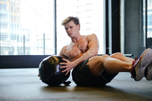 Young Athletic man shakes press with fit ball Stock photo © deandrobot