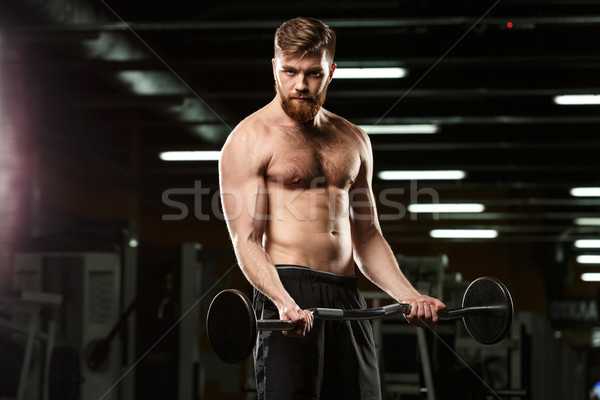 Concentrated sports man make sport exercises with barbell Stock photo © deandrobot