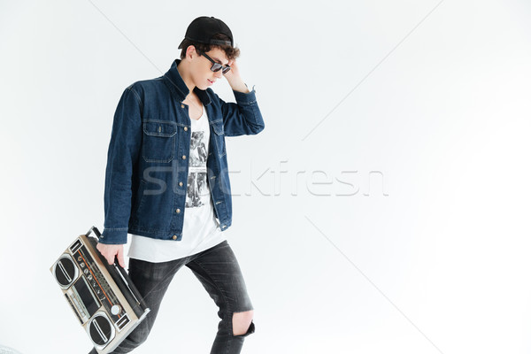 Attractive young man wearing glasses holding boombox. Stock photo © deandrobot