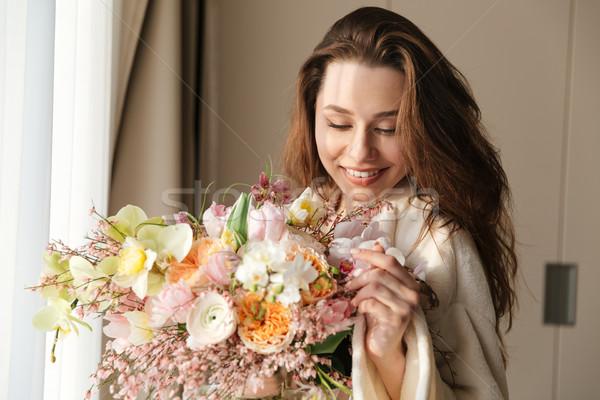 Mosolygó nő virágcsokor virágok otthon mosolyog gyönyörű Stock fotó © deandrobot