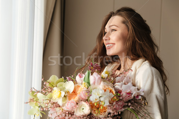 Cheerful woman in bathrobe with boquet of flowers at home Stock photo © deandrobot