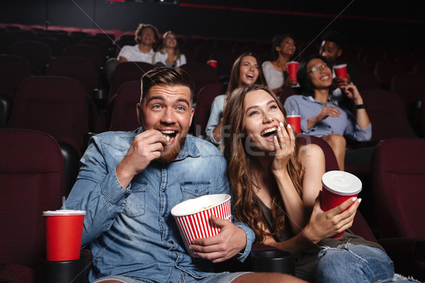 Heureux couple manger popcorn rire séance Photo stock © deandrobot