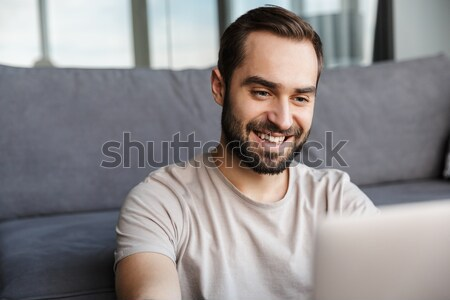 Smiling man reading book. Looking aside. Stock photo © deandrobot