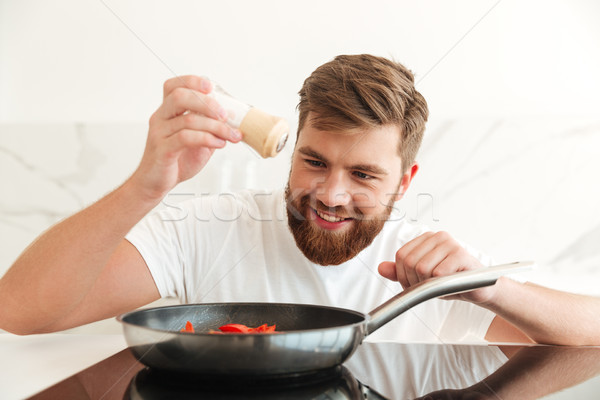 Smiling bearded man sprinkle with salt of vegetables Stock photo © deandrobot