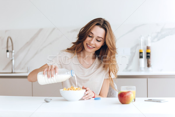 Pretty healthy woman add milk to her breakfast Stock photo © deandrobot