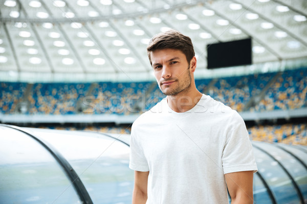 Handsome young sportsman walking at the stadium Stock photo © deandrobot