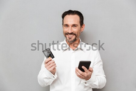 Smiling young man holding gazette and mobile phone. Stock photo © deandrobot