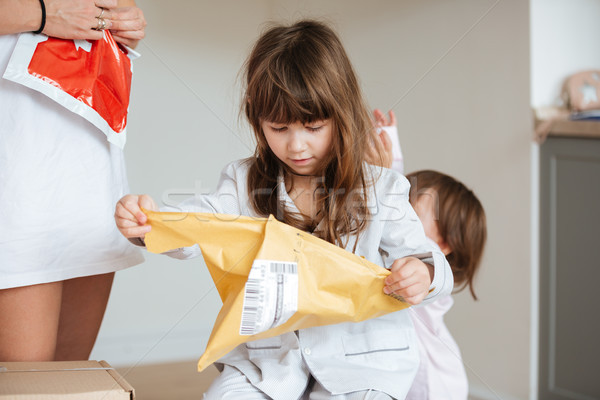 Girl tearing up a package at home Stock photo © deandrobot