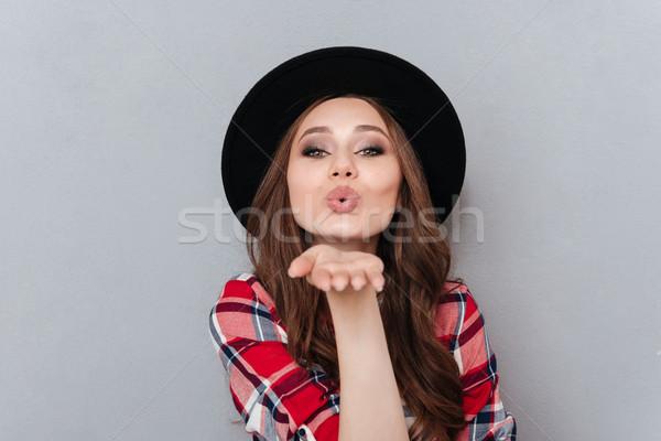 Pretty woman in hat and plaid shirt sending air kiss Stock photo © deandrobot