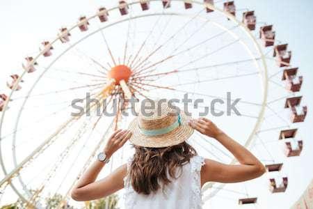 Giovane ragazza Hat piedi vista posteriore parco di divertimenti Foto d'archivio © deandrobot