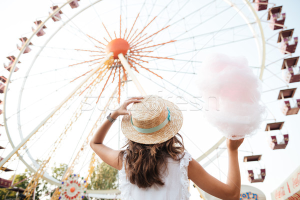 Back view of a girl in hat holding cotton candy Stock photo © deandrobot