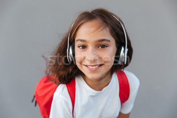 Close up image of happy brunette schoolgirl listening music Stock photo © deandrobot