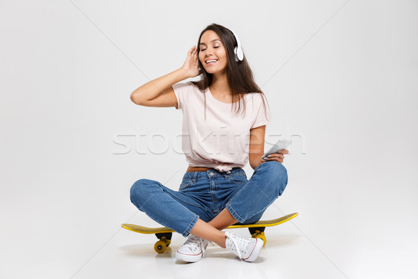 Portrait of cute girl in white headphone listening to music, wit Stock photo © deandrobot