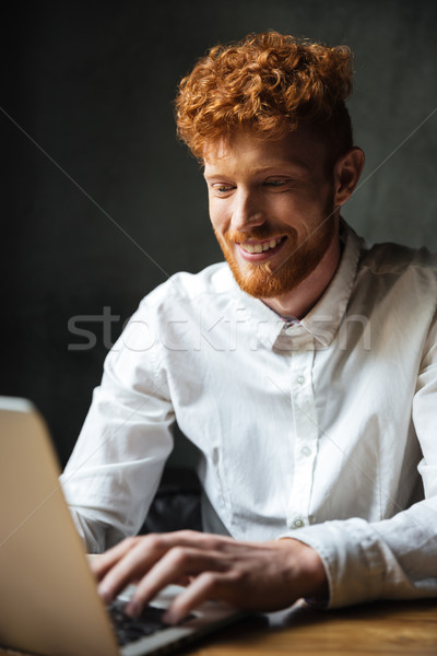 Portrait of a happy young man typing on a laptop Stock photo © deandrobot