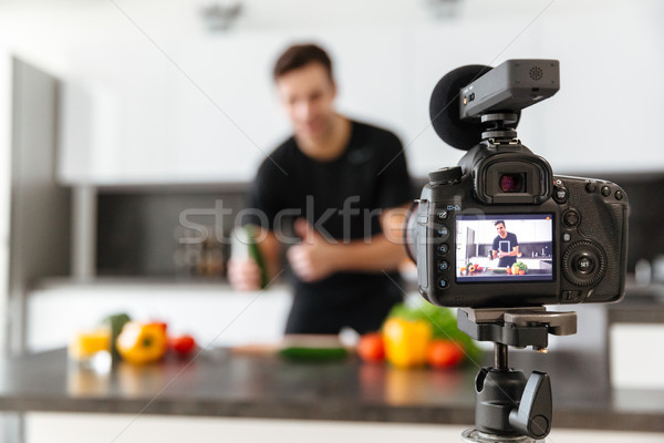 Close up of a video camera filming young smiling male blogger Stock photo © deandrobot