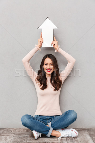 Portrait of attractive young woman holding paper arrow sign up a Stock photo © deandrobot