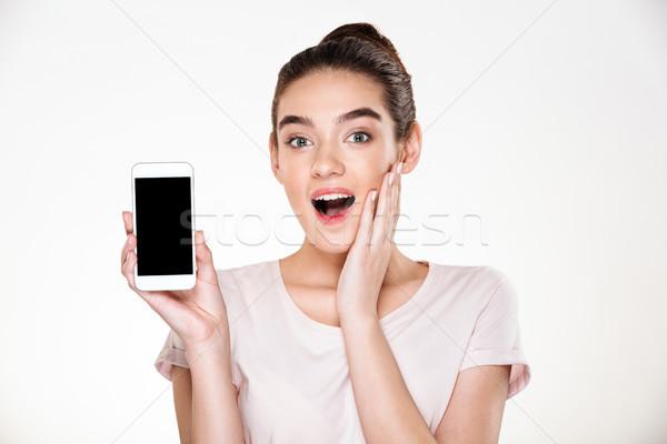 Portrait of successful brunette female 30s rejoicing her new mod Stock photo © deandrobot