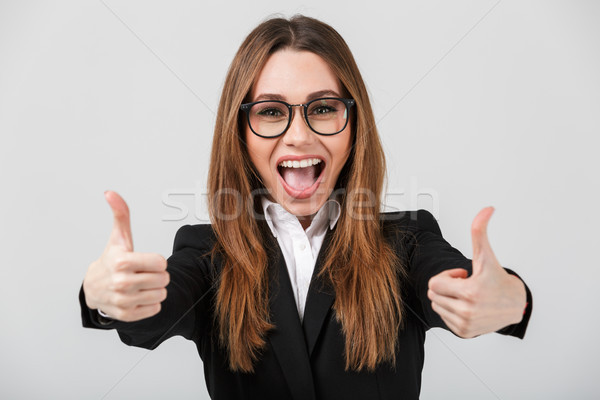Happy cheerful lady showing thumbs up isolated over greywall Stock photo © deandrobot