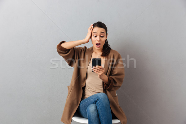 Portrait of an astonished casual asian woman Stock photo © deandrobot