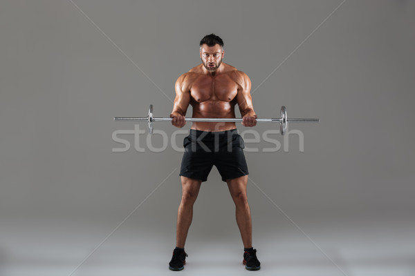 Full length portrait of a muscular strong shirtless male bodybuilder Stock photo © deandrobot