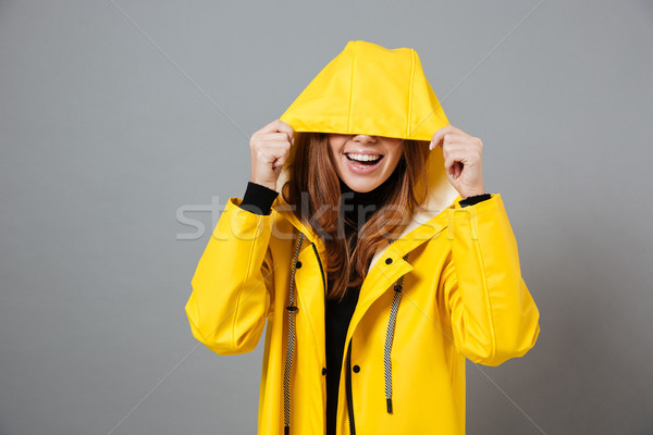 Portrait of a smiling girl dressed in raincoat Stock photo © deandrobot