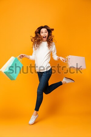 Full-length picture of fashion pretty woman holding packages wit Stock photo © deandrobot