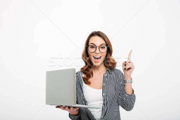 Cheerful young lady using laptop computer have an idea. Stock photo © deandrobot
