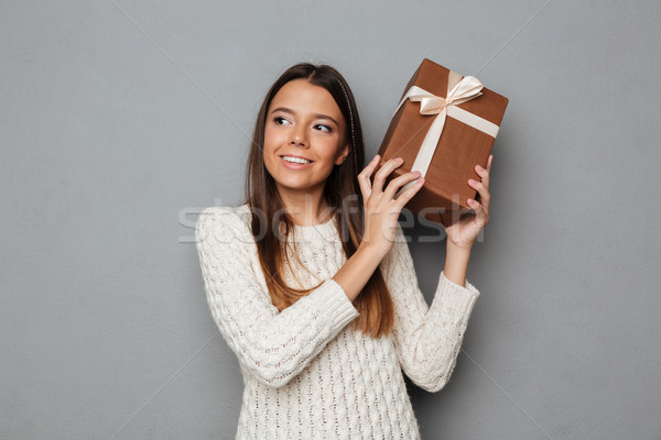 Portrait of a pretty young girl in sweater holding present Stock photo © deandrobot