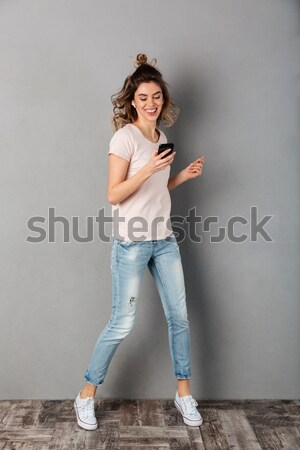 Full length of a cheery young asian woman waving hand Stock photo © deandrobot