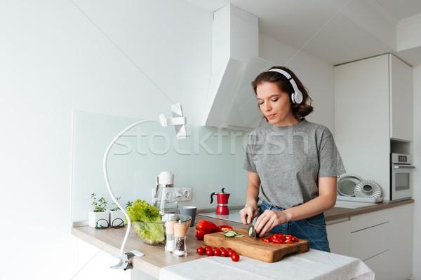 Portrait joli jeune femme écouter de la musique casque cuisson Photo stock © deandrobot