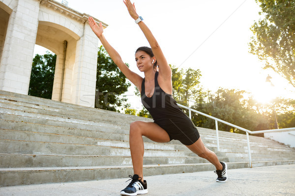 Portré koncentrált fitnessz nő fülhallgató nyújtás lépcsősor Stock fotó © deandrobot