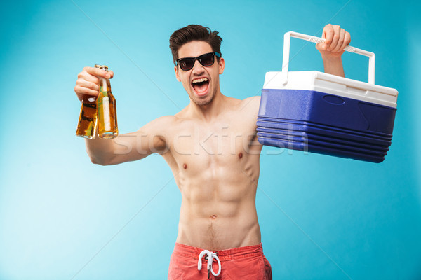 Portrait if a cheerful shirtless man in swimming shorts Stock photo © deandrobot
