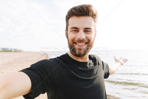 Happy young sportsman with headphones taking a selfie Stock photo © deandrobot