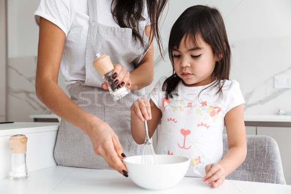 Photo closeup of housewife in apron with her little daughter coo Stock photo © deandrobot