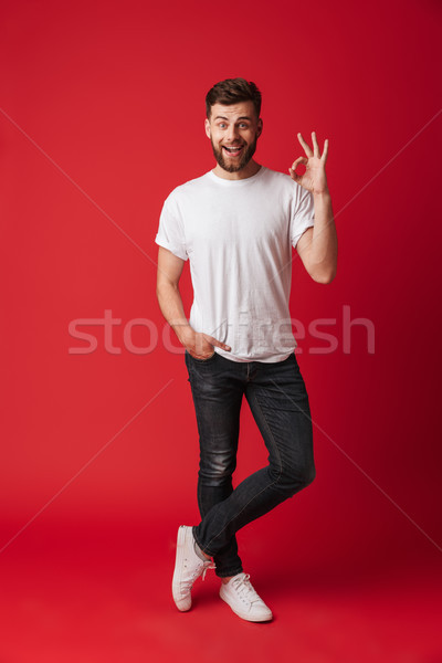 Handsome happy young man showing okay gesture. Stock photo © deandrobot