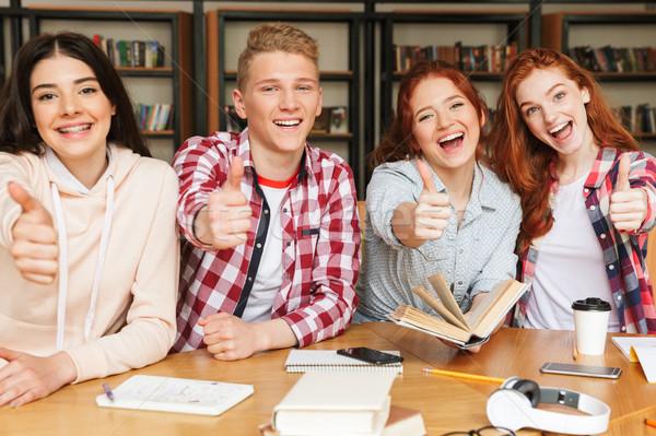 Grupy podniecony nastolatków praca domowa posiedzenia biblioteki Zdjęcia stock © deandrobot
