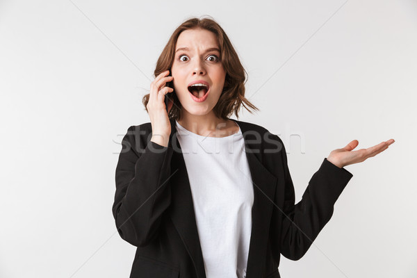 Shocked young woman standing isolated talking Stock photo © deandrobot