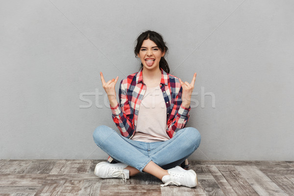 Emotional young lady student make rock gesture showing tongue. Stock photo © deandrobot